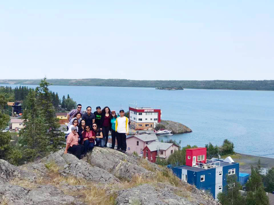Young adult volunteers standing on top of a large rock overlooking houses and a lake